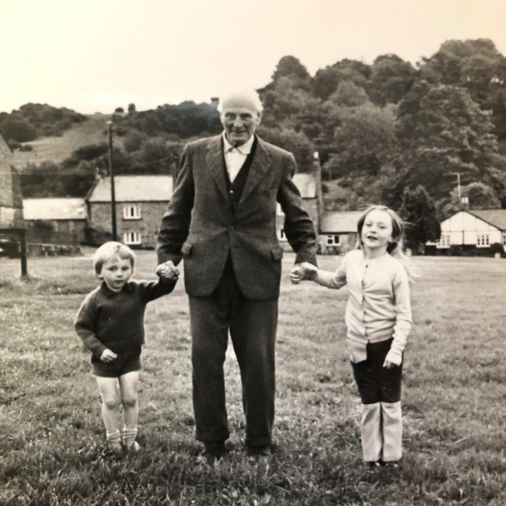 black and white photo of a village with an old man and two small children